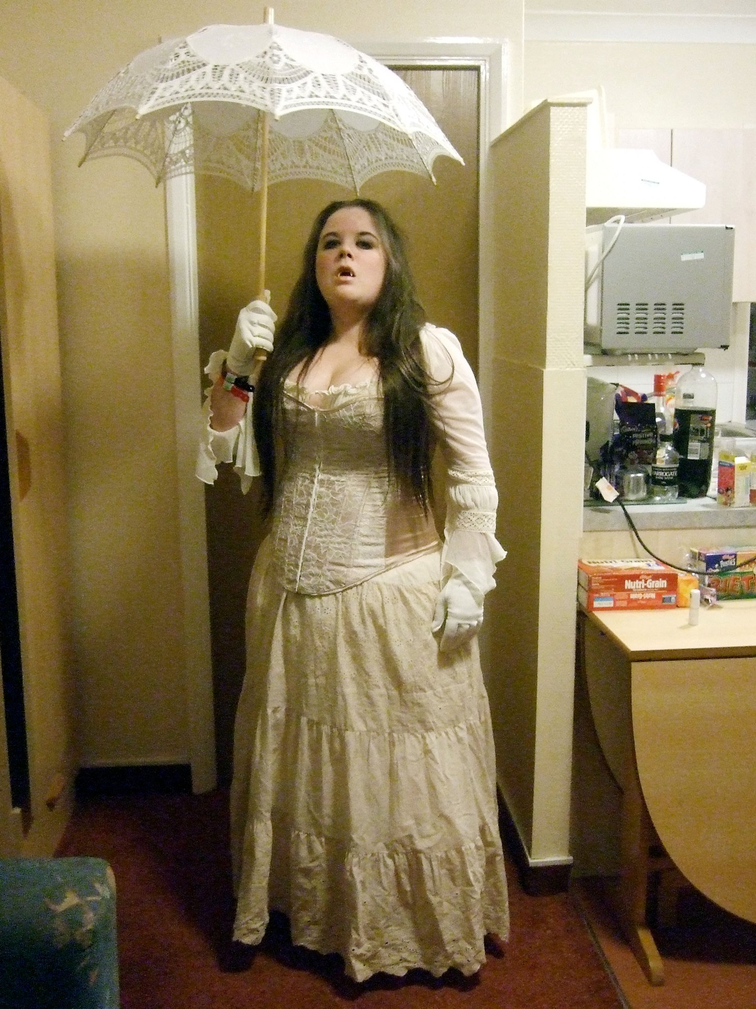 A woman dressed all in white, holding a white parasol above her head. She is wearing vampire fangs