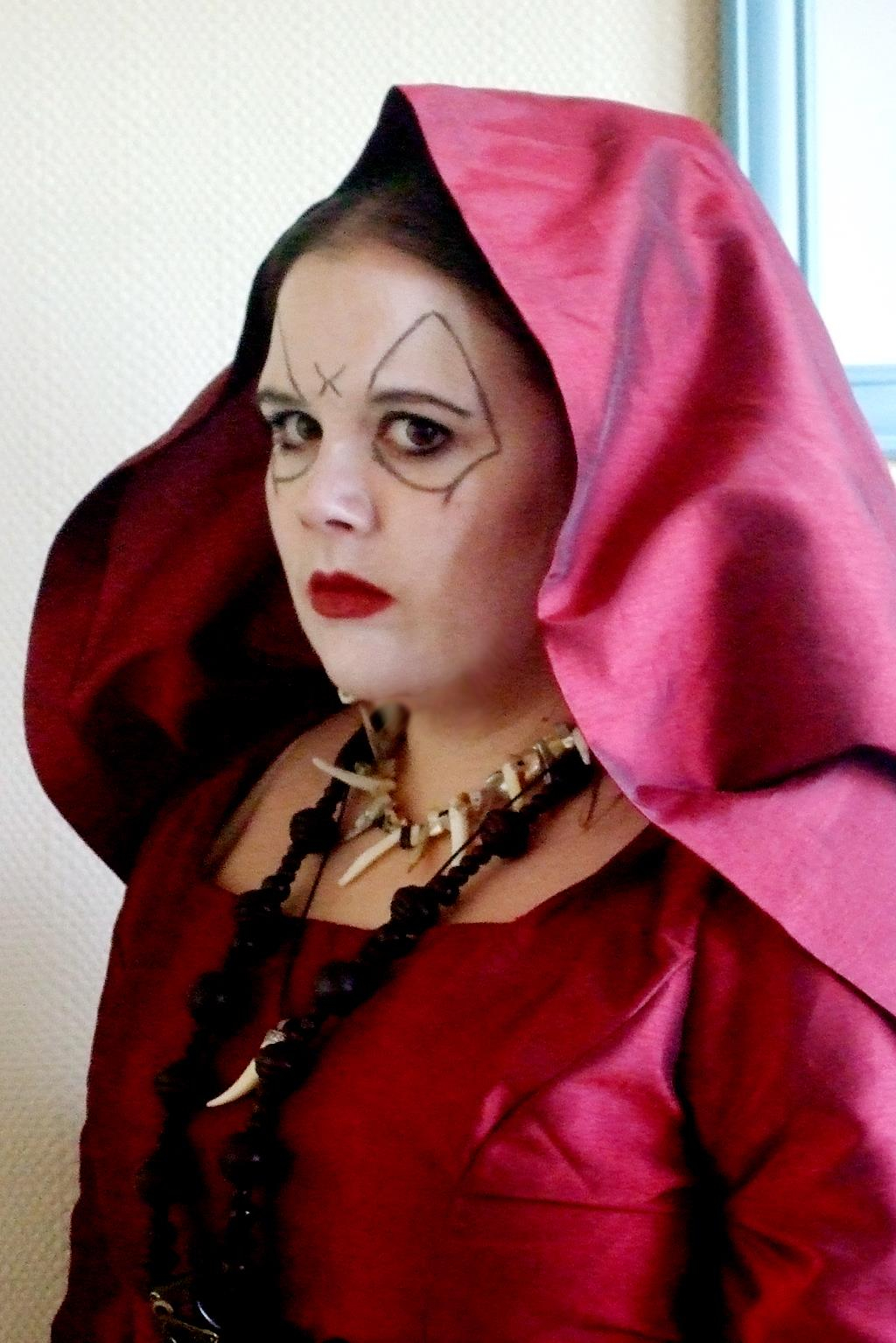 Head and shoulders shot of a woman, wearing a deep red satin costume with a hood. Her face is painted white, with black markings