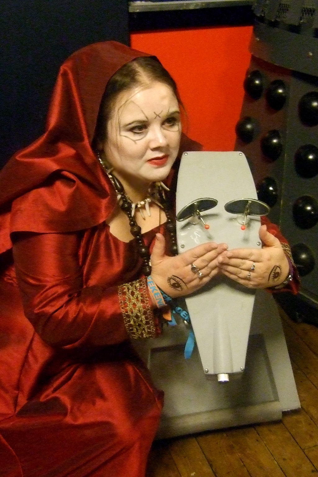 A woman dressed in a red satin outfit, with facepaint on her face, crouched down next to a robot dog