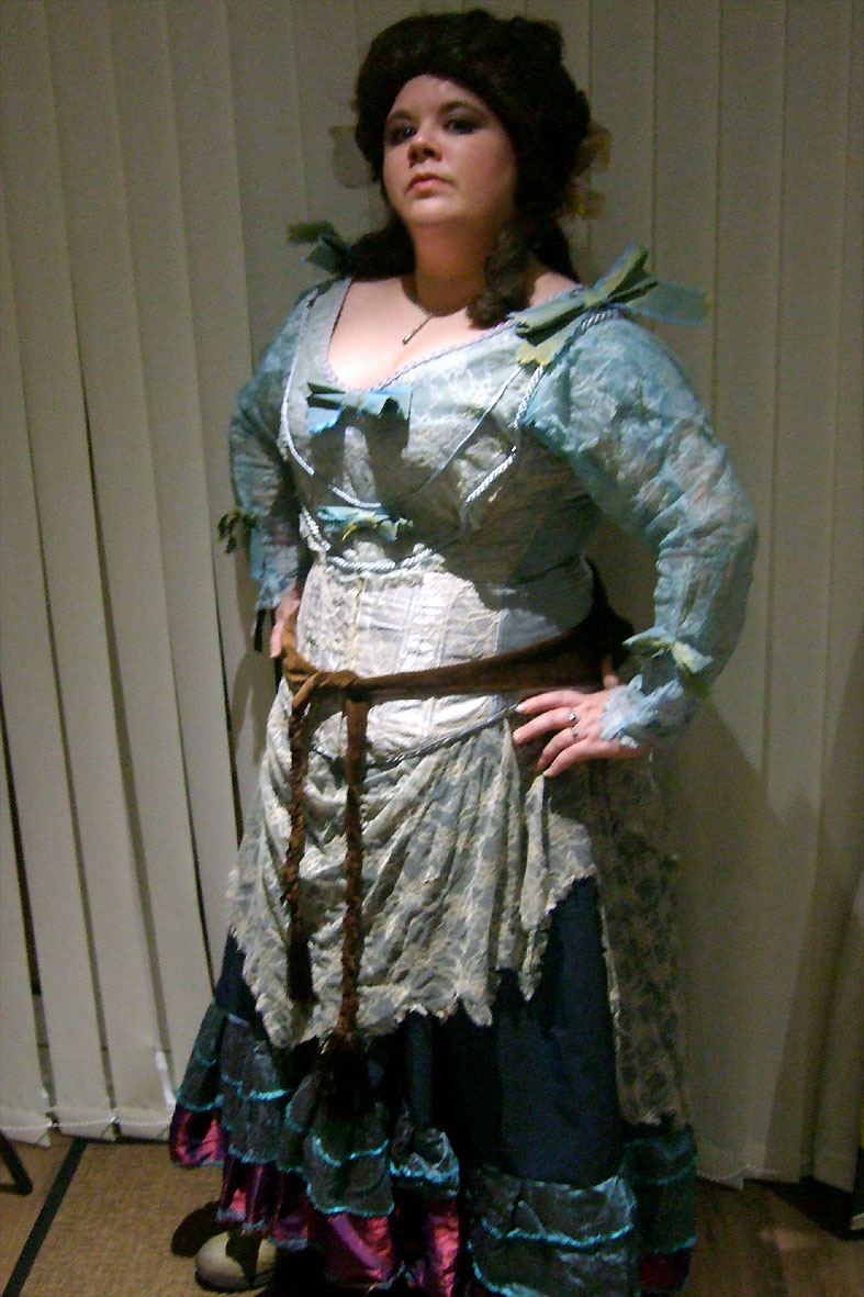 A woman stands, hands on hips, in a mismatched tattered outfit, including a blue corset and dark blue period skirt. She wears a large brunette untidy wig